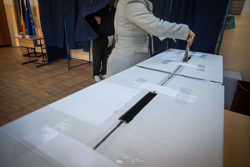 image of a woman voting in a polling place